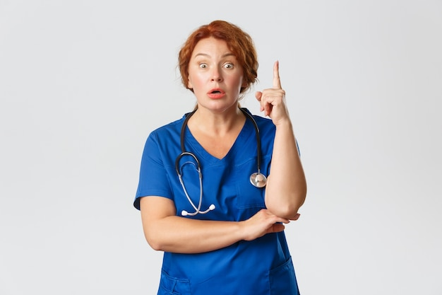 Overwhelmed redhead female doctor, middle-aged nurse in scrubs have suggestion, saying idea or plan, raising index finger eureka gesture with worried expression, standing