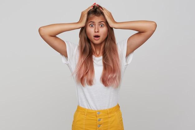 Ошеломленная молодая симпатичная женщина со светло-каштановыми длинными волосами, схватившаяся за голову руками и изумленно приподнимая брови, стоя над белой стеной с открытым ртом