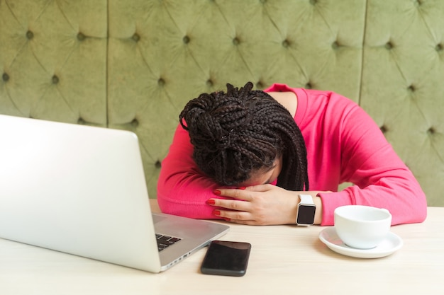 Переутомление и сон. портрет усталого доброго красивого молодого фрилансера с черными дредами в розовой блузке сидит в кафе и засыпает на столе после слишком долгой работы. в помещении
