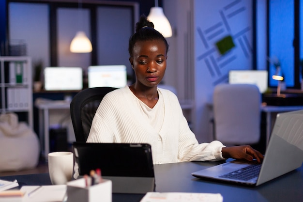 Overworked african businesswoman checking charts on tablet pc late at night