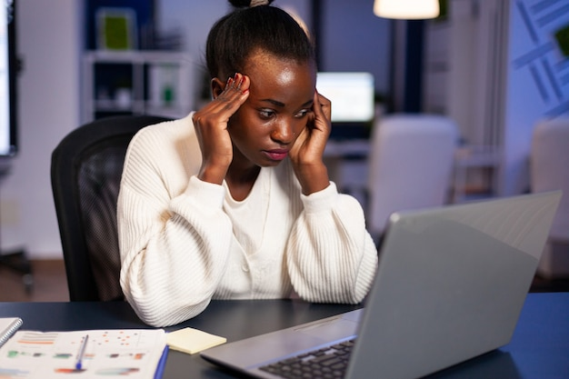 Overworked black businesswoman looking worried at laptop rubbing temples