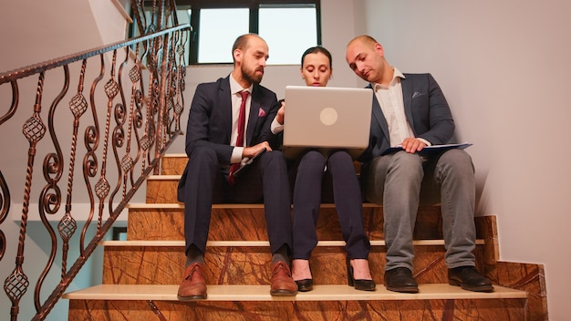 ラップトップとタブレットを使用して階段に座って残業し、困難な財務プロジェクトを分析している過労の同僚。会社の建物の階段の会社のマネージャーおよびオフィスの幹部。