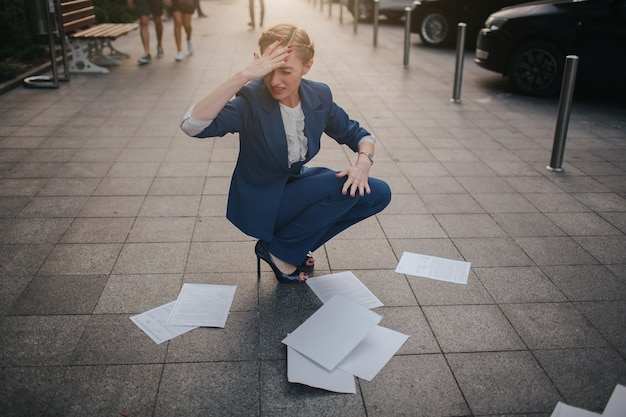 書類の多くを持っている過労のビジネス女性。たくさんの書類に囲まれたビジネスウーマン。書類の山に立っている女性実業家。