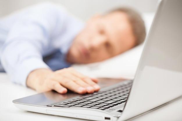 Переутомленный бизнесмен. человек с седыми волосами в строгой одежде, держащий руку на клавиатуре ноутбука во время сна в постели