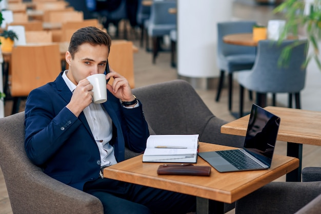 Overworked businessman have coffee break and speaking on smartphone