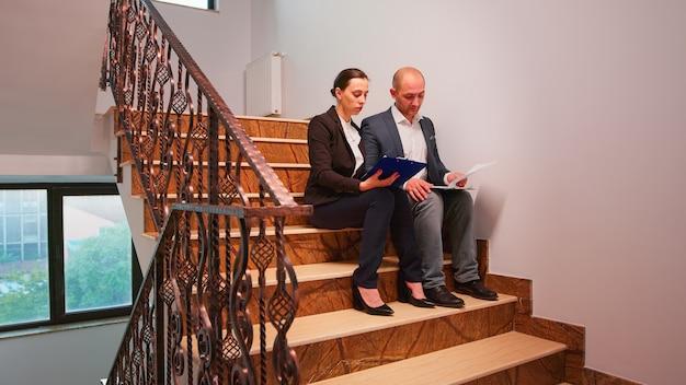 過労のビジネスマンは、同僚が階段に座って、締め切りの金融危機についての報告書を読んでいます。困難なプロジェクトを説明する企業の仕事で夕方に一緒に働く同僚の起業家。
