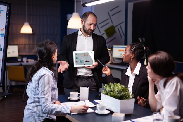 Uomo d'affari oberato di lavoro che mostra la presentazione di grafici finanziari utilizzando idee aziendali di brainstorming su tablet
