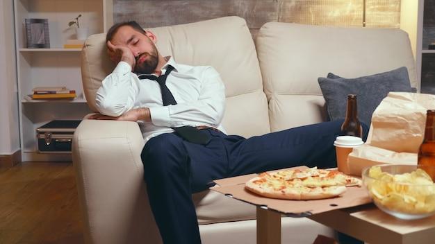 ソファで寝ている過労ビジネスマン。テーブルの上のファーストフード。