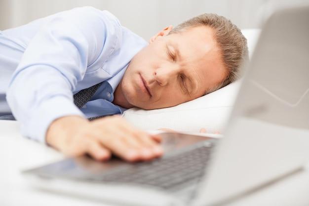 Переутомленный бизнесмен спит. старший мужчина в формальной одежде, держащий руку на клавиатуре ноутбука во время сна в постели