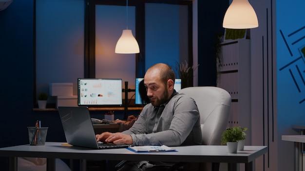늦은 밤에 신생 기업 사무실에서 일하는 노트북에 과로한 사업가가 관리 전략을 입력합니다. 피곤에 지친 매니저는 경제 통계를 분석하는 회사 방에 혼자 남겨졌다