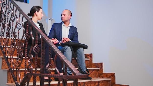 休憩を取っている企業の営業所の階段に座って議論している過労のビジネスマン。深夜に一緒に残業をしている同僚の起業家が締め切りプロジェクトの計画を立てる