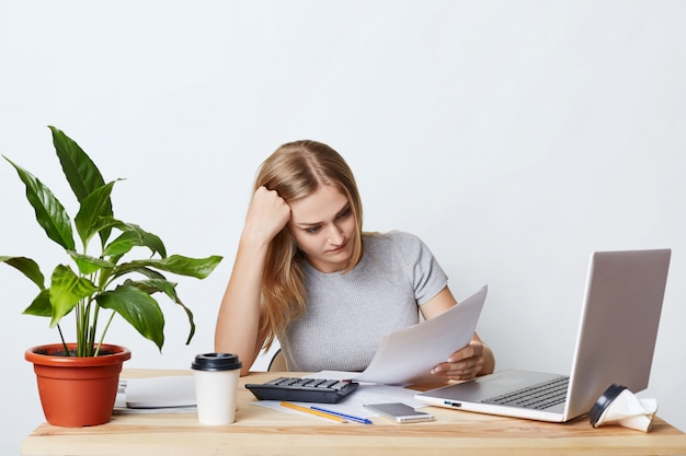 Overworked businesswoman sitting at wooden table, surrounded with modern gadgets, reading documents attentively, trying to understand everything. female accounter calculating bills and expenses