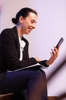 プロジェクトの締め切りについてのビデオ通話中に微笑んでいる働き過ぎの実業家。階段に座ってビデオ通話のためにスマートフォンを使用してクライアントと話している起業家。