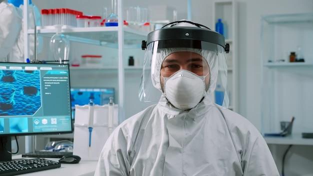 카메라를 보고 피곤해 보이는 작업복을 입고 현대적인 시설을 갖춘 실험실에 앉아 있는 과로한 화학자. 백신 개발을 위한 첨단 화학 도구를 사용하여 바이러스 진화를 조사하는 의사 팀