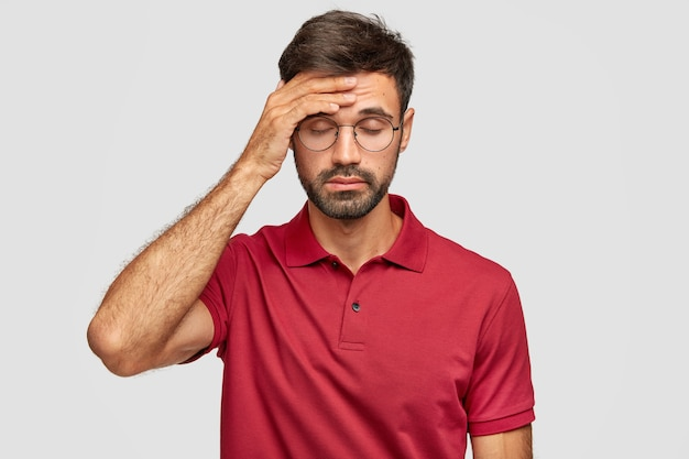 Overworked cuacasian male feels terrible headache after sleepless night, keeps hand on forehead, shut eyes, dressed in casual red t-shirt, stands against white wall. people and tiredness