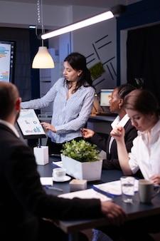 深夜にマーケティング戦略をブレインストーミングする事務室の会議室で働く企業の集中した多様なビジネスマンの過労