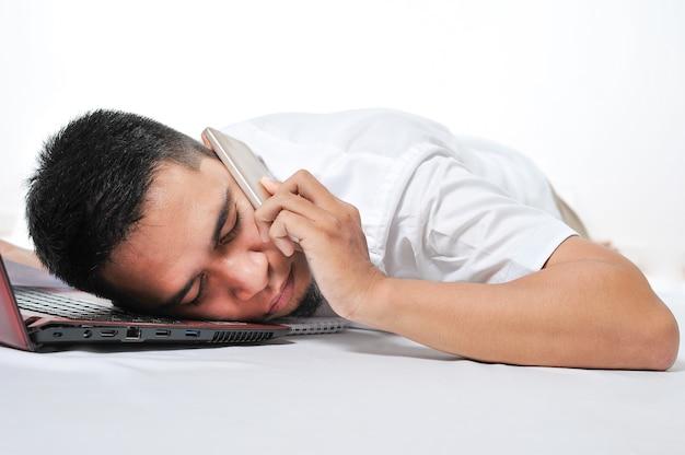 Перегруженный фрилансер молодой азиатский мужчина спит у ноутбука и телефона на ушах на работе устал и перегружен, изолированные на белом фоне