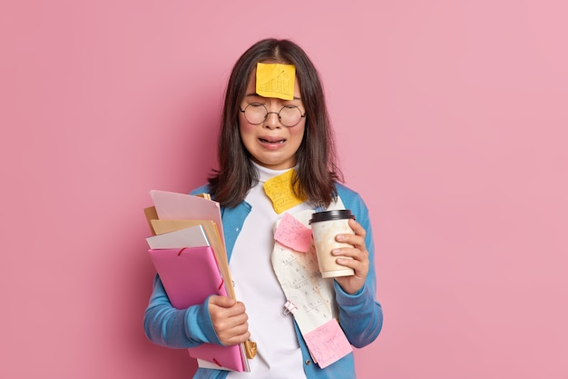Overworked frustrated female accountant has much remote work surrounded with paper documents drinks coffee to go cries from despair.