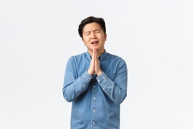 Overworked gloomy and sad asian man begging for help, holding hands together over chest in praying gesture, asking favour, showing remorse, standing white background overwhelmed.