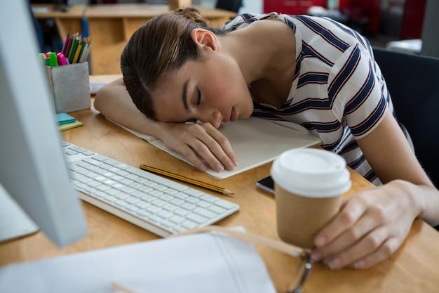 彼の机で寝ている過労のグラフィックデザイナー