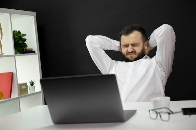 Overworked handsome businessman in white shirt with closed eyes and hands on back of head
