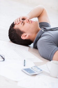 Overworked man. top view of depressed young man holding hand on forehead while lying on the floor with documents and coffee cup on it