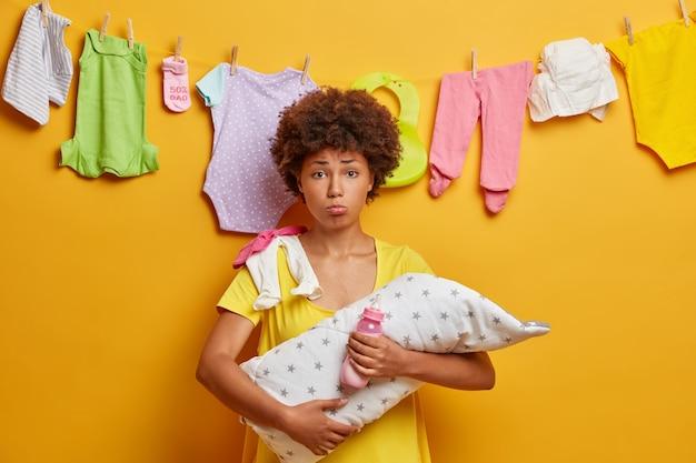 過労のマルチタスクの母親は、子供を手に持ってポーズをとり、乳児の世話をするのに忙しく、新生児の育成の経験がなく、黄色い壁に隔離された貴重な小さな赤ちゃんを抱いています。家族、母性