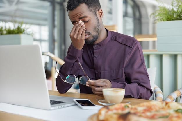 Перегруженный работой профессиональный экономист мужского пола, держит очки, устал много часов работать за портативным компьютером, у него болит голова после усталого рабочего дня