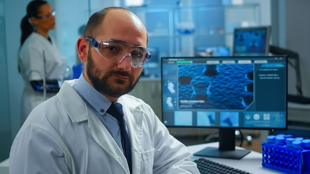 Overworked scientist with protection glasses looking at camera sighing sitting in research laboratory. doctors examining virus evolution using high tech and chemistry tools for medical research.