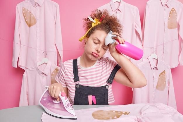 働き過ぎの眠そうな女性の家政婦が額を拭くと、家事用アイロンをかけている間、家事はすべてを終えるために急いでいるスプレーボトルの焼けたシャツを保持します。