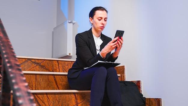 スマートフォンを使用して締め切りプロジェクトの残業をしている過労ストレス実業家。深夜にビジネスビルの階段に座って企業の仕事に取り組んでいる真面目な起業家。