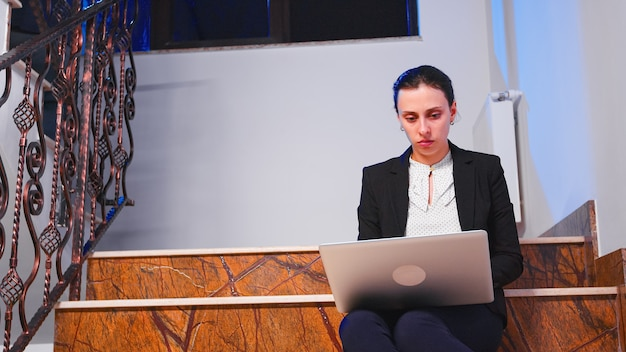 過労ストレスの実業家は、ラップトップのビジネスの締め切りに夜遅くまで働いています。残業中のビジネスビルの階段に座って企業の仕事をしている真面目な起業家。