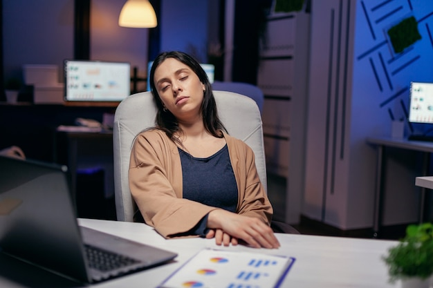 과로 스트레스를 받은 여성은 마감 시간에 등받이 지지대를 누워 자고 있습니다. 직원은 중요한 회사 프로젝트를 위해 사무실에서 혼자 밤늦게까지 일하다가 잠이 듭니다.