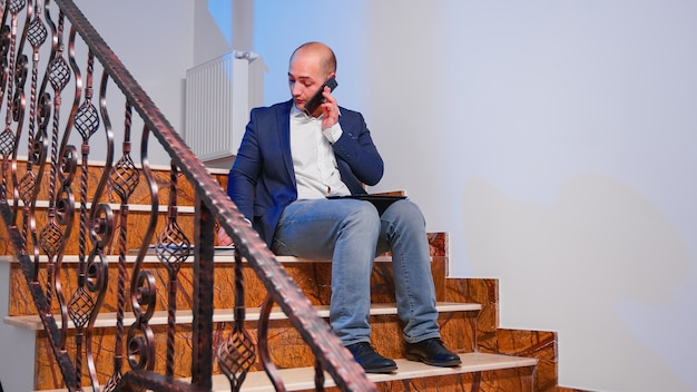 Overworked tired businessman reading project deadline during phone call with corporate manager. serious entrepreneur working on job sitting on staircase of business building late at night.