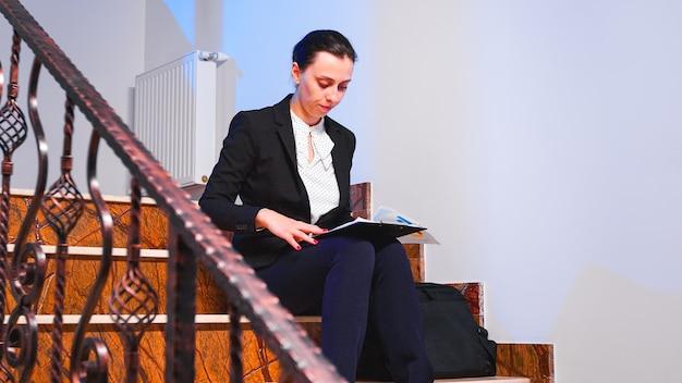 ビジネスビルの階段に座って夕方に締め切りプロジェクトの財務報告書を読んで過労疲れた実業家。深夜に残業している真面目な起業家