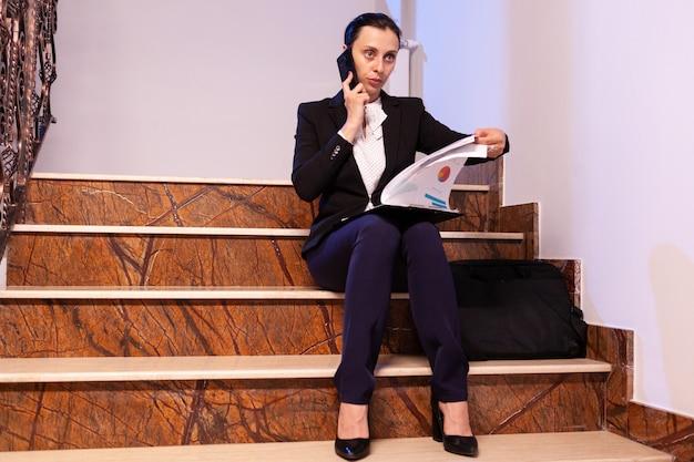 직장 동료와 전화 통화를 하는 동안 과로한 피곤한 사업가가 프로젝트 마감일을 읽었습니다. 야간에 업무용 건물 계단에 앉아 작업 프로젝트를 진행하는 진지한 기업가입니다.