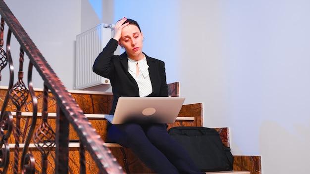 ビジネスビルの階段に座っているラップトップを使用して困難なプロジェクトの締め切りに取り組んでいる頭痛で過労疲れた実業家。真面目な起業家が深夜に企業の仕事をしている。