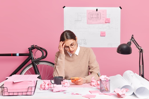 Overworked tired female architect focused at smartphone has much work to do works on architectural project makes sketches draws sketches poses in coworking space against pink wall. office worker
