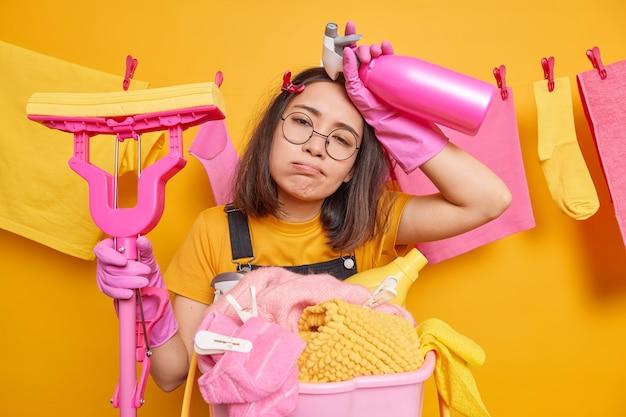 過労で疲れた若いアジア人主婦は、モップを持ってモップを握り、掃除用洗剤は家の仕事をするのに忙しいです。