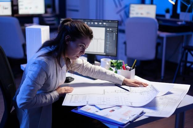 과로한 여성 건축가는 컴퓨터 앞에 있는 사무실 책상에 앉아 청사진을 확인하고 일치시킵니다.