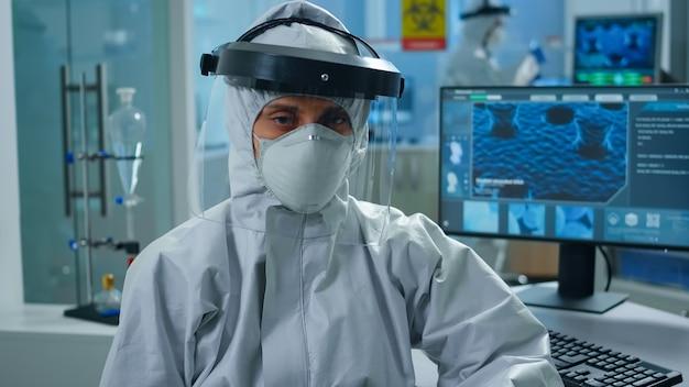 モダンな設備の整ったラボに座っている過労の女性化学者は、前で疲れているように見えるつなぎ服を着ています