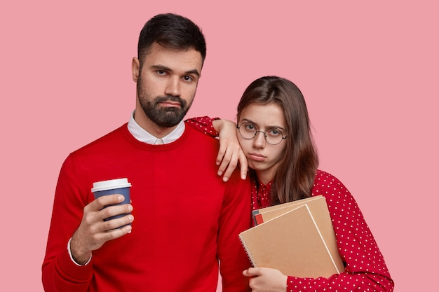 Overworked woman and man have sad expressions, carry notepads, takeaway coffee, dressed in red clothes