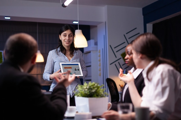 태블릿을 사용하여 마케팅 그래프를 보여주는 과로한 워커홀릭 기업가 여성