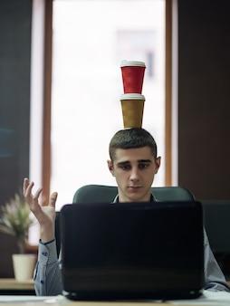 과로. 마감 시간. 비즈니스 라이프 스타일. 노트북 뒤에 앉아 그의 머리에 coffeee 잔을 들고 남자.