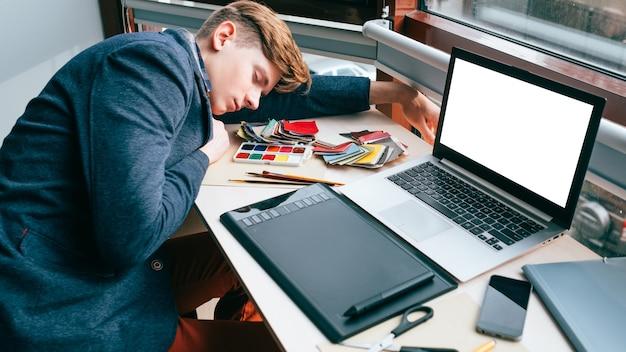 과로 피로. 직장의 책상에서 자고 피곤한 디자이너. 비효율적 인 작업 계획. 그래픽 태블릿, 흰색 화면이있는 노트북