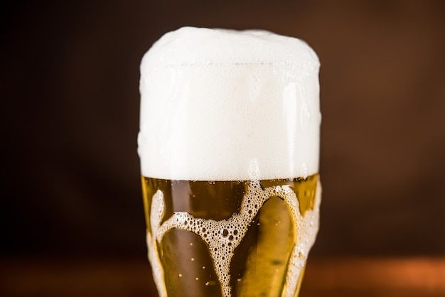Холодное пиво в бокале на столе с пенистой пеной overyflow