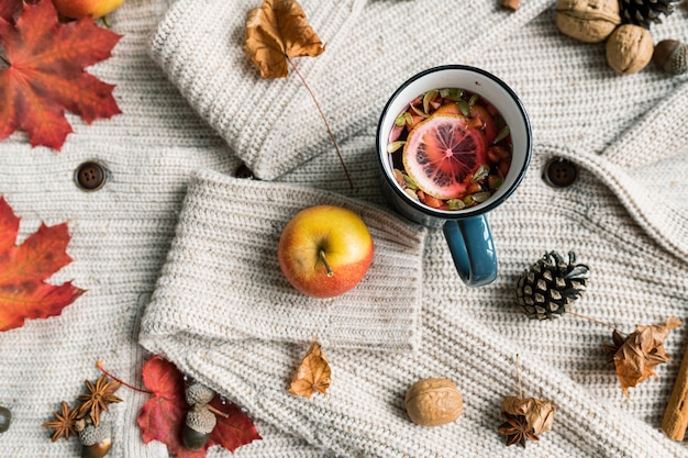 Oveview of ripe apple, mug of hot herbal tea with lemon