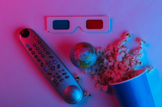 Ovie time cardboard bucket of popcorn tv remote and stereoscopic anaglyph disposable paper 3d glasses globe in pink blue gradient neon light top view