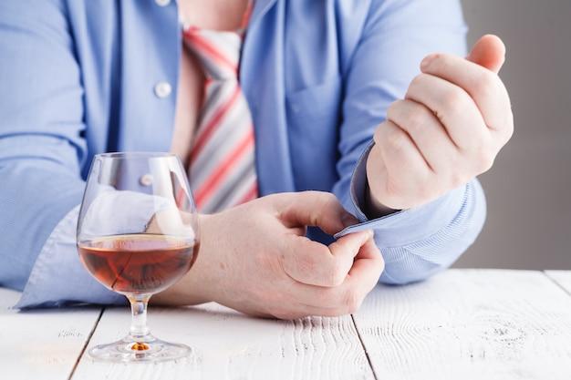 男は手にガラスowウイスキーを保持します。