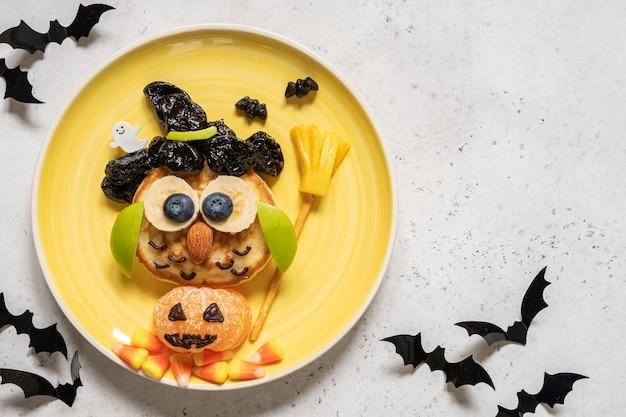 ハロウィーンの子供の朝食のための果物とフクロウのパンケーキ